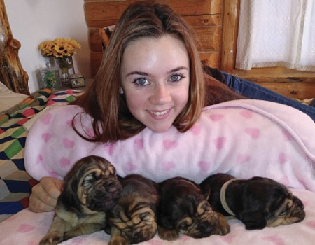 Karissa smiles with some pups from her recent litter.